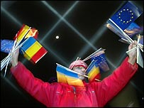 A Romanian youth holds EU and Romanian flags at a New Year party in Bucharest