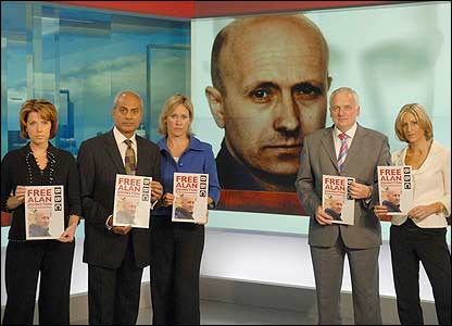 BBC television news readers hold up posters of Alan Johnston - 20/06/07