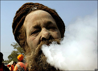 A Naga Sadhu, or Hindu holy man, smokes tobacco during a procession towards Sangam in Allahabad