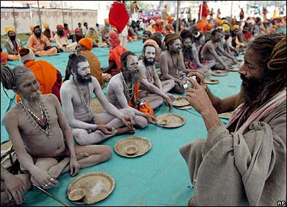 A Naga Sadhu, or a Hindu holy man, takes a picture of his colleagues as they wait for the food before a procession toward Sangam in Allahabad