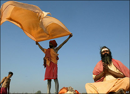 A Sadhu or Hindu holy man, right, prays, as two others dry their clothes after having a swim at the Mela site