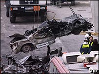 A flattened car is removed from the rubble of Barajas airport car park