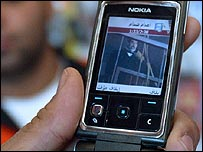 Iraqi watches video of Saddam Hussein's execution on a mobile phone handset
