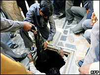 Workers and Police retrieve evidence including body parts and clothing from a drain in Noida