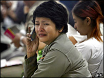 A woman waits for news at the airport in Surabaya
