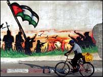 A man cycles past a mural showing militant symbols