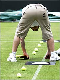 A Hawk-Eye technician helps prepare Court One at Wimbledon for calibration