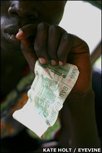 Young girl holding a 1,000 Sudanese dinar note (�2.50; $4.80)