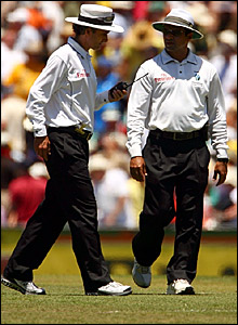 Umpires Billy Bowden and Aleem Dar take the players off for lunch on day three