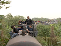 Illegal immigrants ride on top of a freight train