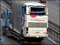 National Express coach is taken away on the back of a lorry