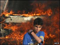 Palestinian boy in front of burning van