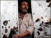 Un iraquí recostado en una pared baleada