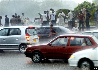 Pakistanis walking in the rain as they on a flooded street in Karachi