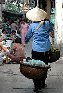 Woman wearing traditional conical hat walking down the street