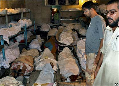 Pakistani workers of Edhi Foundation stand beside the dead bodies of the victims of Saturday's heavy rains and thunderstorms, at a morgue in Karachi