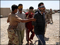 An Iraqi soldier leads away suspected militants captured in Baquba