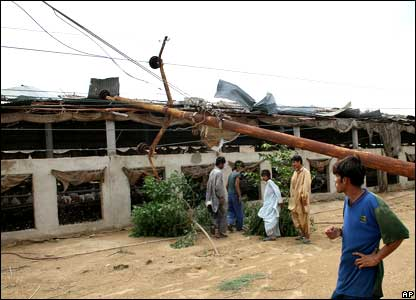 Local residents stand beside an electric pole fallen over a building caused by Saturdays heavy rains and thunderstorms in Ghadab area outskirt of Karachi,