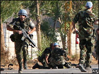 A Spanish UN peacekeeper runs as another Spanish soldier assists an injured colleague near the southern Lebanese village of Marjayoun