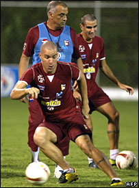 Venezuelan footballer Jose Rey (front) controls the ball in front of coach Richard Paez during a training session