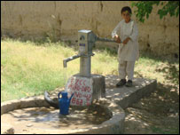 A young Afghan boy uses a new well built by British troops