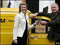 AA patrol Andy McMorran presents AA member Crystal Walter with a commemorative historical AA badge outside her home in Earl's Court, London, after becoming the 100 millionth member to call on the AA