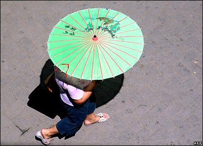 Woman carrying parasol in Tirana, Albania