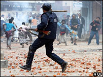 A policeman faces stone-throwing protesters in Dhaka