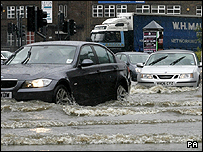 Motorists drive through flood waters after the banks of the River Aire in Leeds city centre are broken by heavy rain fall