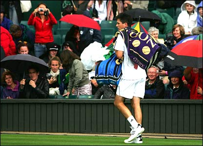 Tim Henman leaves Centre Court for a rain delay