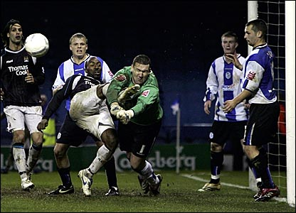 Sheffield Wednesday keeper Mark Crossley (centre) feels the full force of Darius Vassell's boot