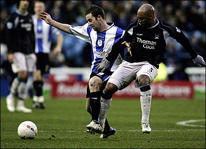 Sheffield Wednesday's Stephen MacLean (left) is held up by Manchester City's Ousmane Dabo
