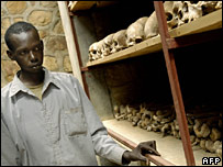 File image of genocide memorial site guardian Theogene Ruzindana on 21 February 2004, next to remains of some of the victims