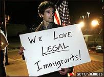 """Un manifestante con un cartel que reza: """"Amamos a los inmigrantes legales"""""""