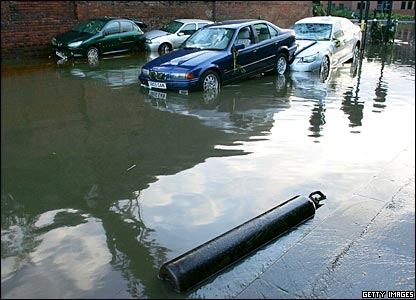 Cars and debris in a flooded road in Sheffield.