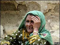 Pakistani woman sits outside her collapsed mud house in Karachi, 25 June 2007