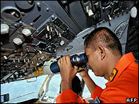 An Indonesian airline crew member helps search for the missing jet on 7 January 2007