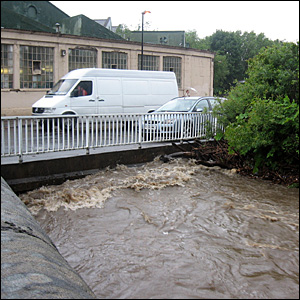 Cars over a bridge with high water below