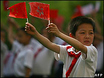 A schoolboy in China waves a Chinese national flag and a Hong Kong Special Administrative Region (SAR) flag at a handover anniversary event in Nanjing, Jiangsu Province