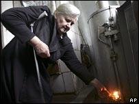 Mujer bielorrusa enciende una estufa de gas