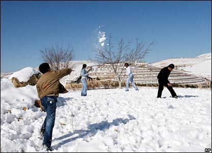 A Syrian child throws a snowball