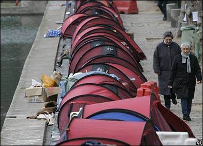 People walk past canal-side tents for the homeless in Paris