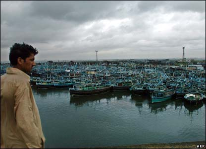 Man looks at empty fishing boats in the city of Karachi