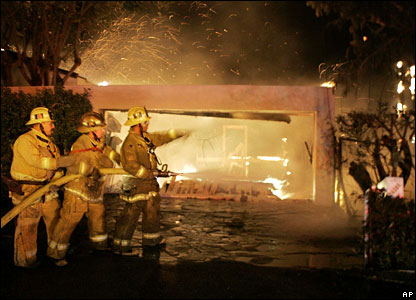 Firefighters train water on a burning home as wind blows embers on Malibu Road