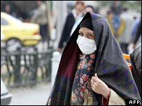A woman wears a mask to protect herself from pollution in central Tehran