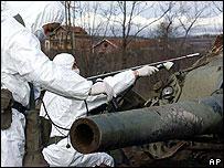 Italian soldiers measure radiation on a Yugoslav tank destroyed in Kosovo