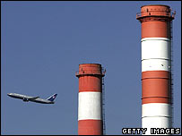 Plane flying past factory chimneys