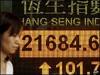 Woman passing electronic board showing stock market data in Hong Kong