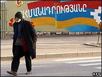 Man walks past mural of flag of breakaway Nagorno-Karabakh region