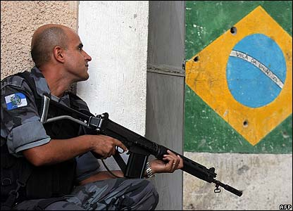 Police officer crouches by a Brazil flag mural